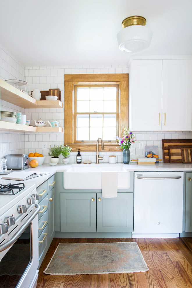Example of a small transitional u-shaped medium tone wood floor and brown floor eat-in kitchen design in Other with a farmhouse sink, shaker cabinets, blue cabinets, quartz countertops, white backsplash, porcelain backsplash, white appliances and a peninsula