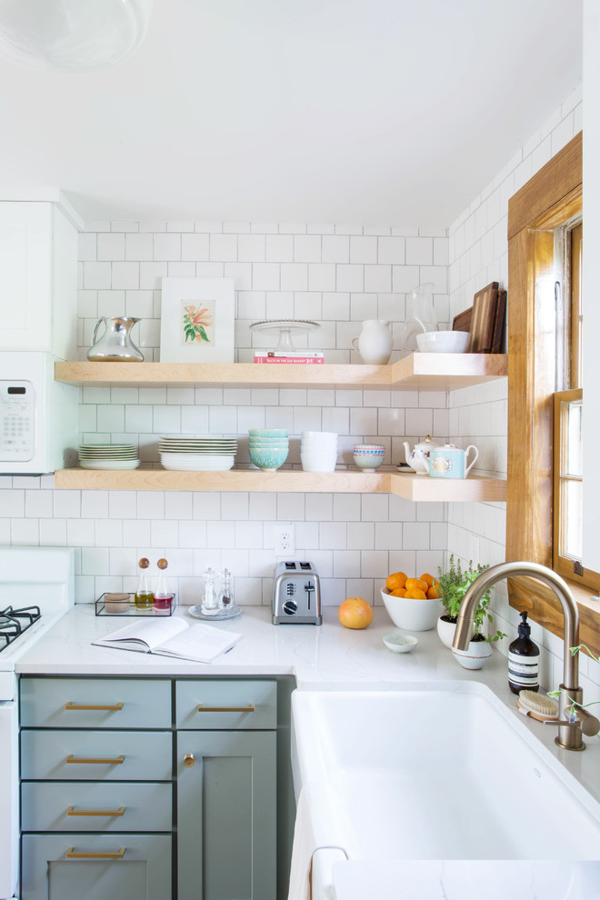 Example of a small transitional l-shaped dark wood floor and brown floor eat-in kitchen design in Other with a farmhouse sink, recessed-panel cabinets, gray cabinets, quartz countertops, white backsplash, subway tile backsplash, white appliances and a peninsula