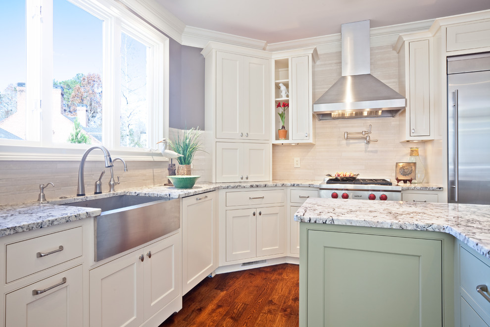 Trendy l-shaped kitchen photo in Atlanta with stainless steel appliances, a farmhouse sink, granite countertops, beaded inset cabinets, white cabinets, beige backsplash and stone tile backsplash