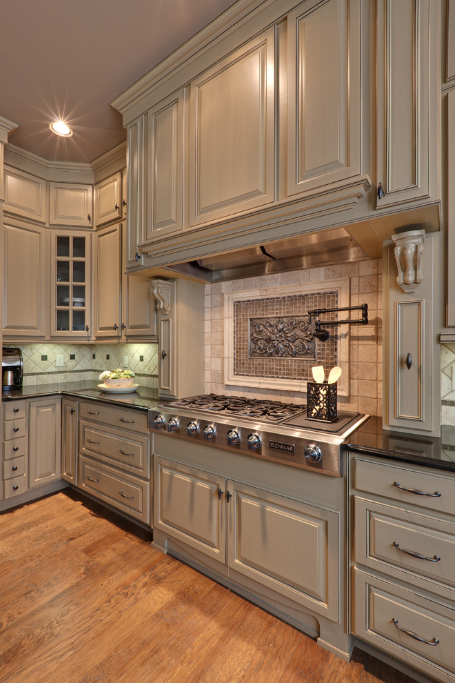 Example of a classic kitchen design in Atlanta with raised-panel cabinets, beige cabinets, beige backsplash and stainless steel appliances