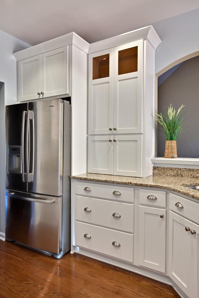Diseño de cocina contemporánea, pequeña, con armarios estilo shaker, puertas de armario blancas, electrodomésticos de acero inoxidable, fregadero de doble seno, encimera de granito, suelo de madera en tonos medios, península, suelo marrón y encimeras beige