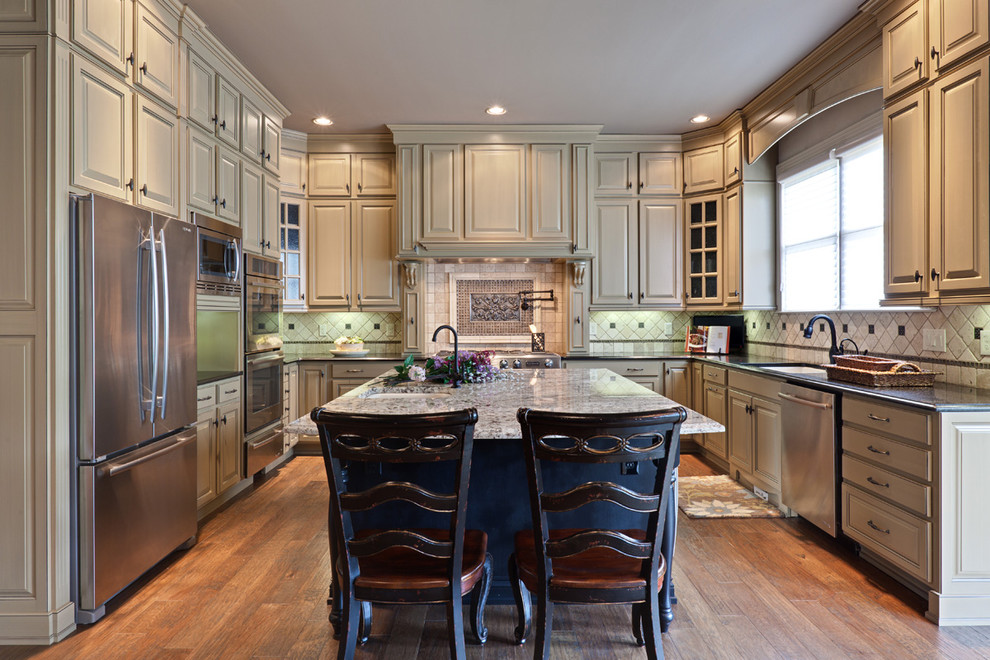 Elegant u-shaped kitchen photo in Atlanta with stainless steel appliances, granite countertops, raised-panel cabinets and beige cabinets