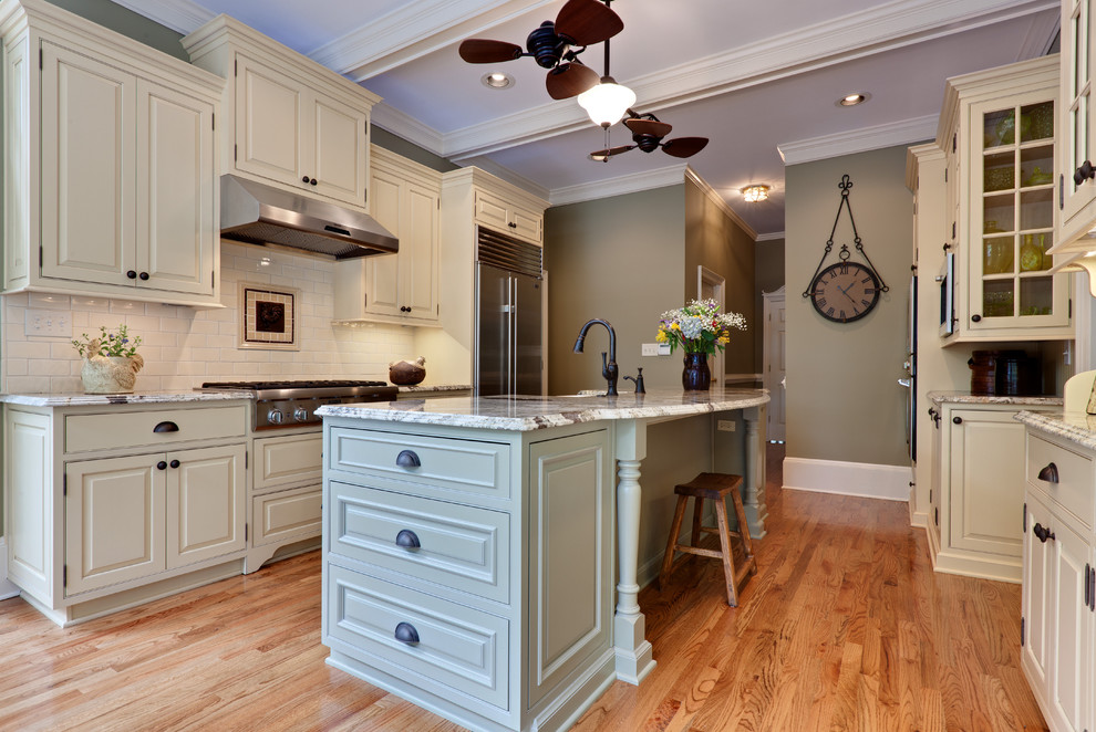 Enclosed kitchen - traditional galley enclosed kitchen idea in Atlanta with beaded inset cabinets, stainless steel appliances, beige cabinets, white backsplash and subway tile backsplash