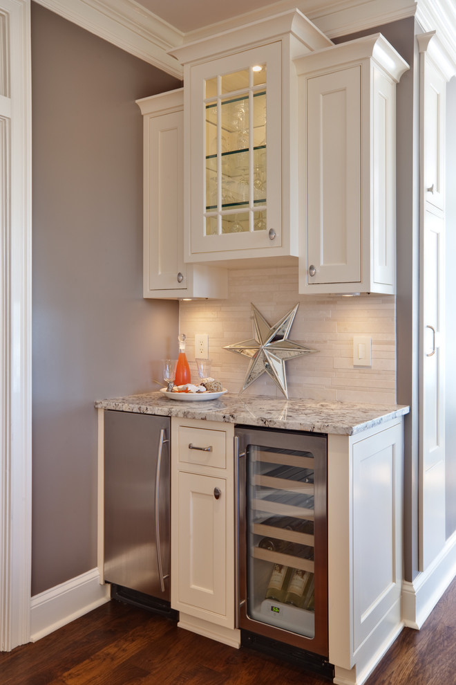 Elegant kitchen photo in Atlanta with shaker cabinets, white cabinets, granite countertops, beige backsplash and stainless steel appliances
