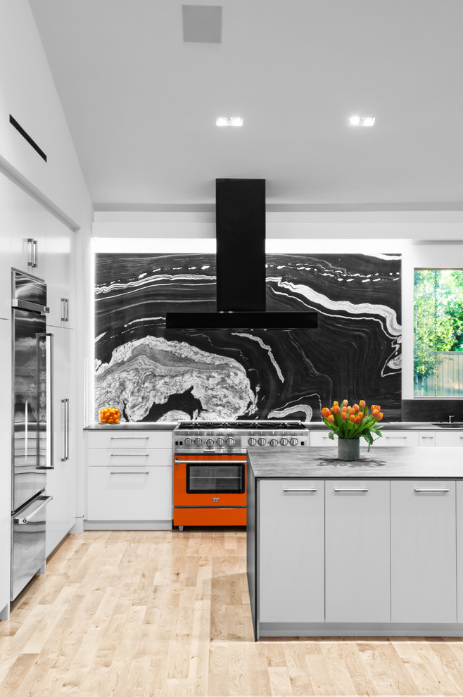 Example of a 1960s l-shaped light wood floor and beige floor kitchen design in Houston with an undermount sink, flat-panel cabinets, gray cabinets, black backsplash, stone slab backsplash, stainless steel appliances and an island