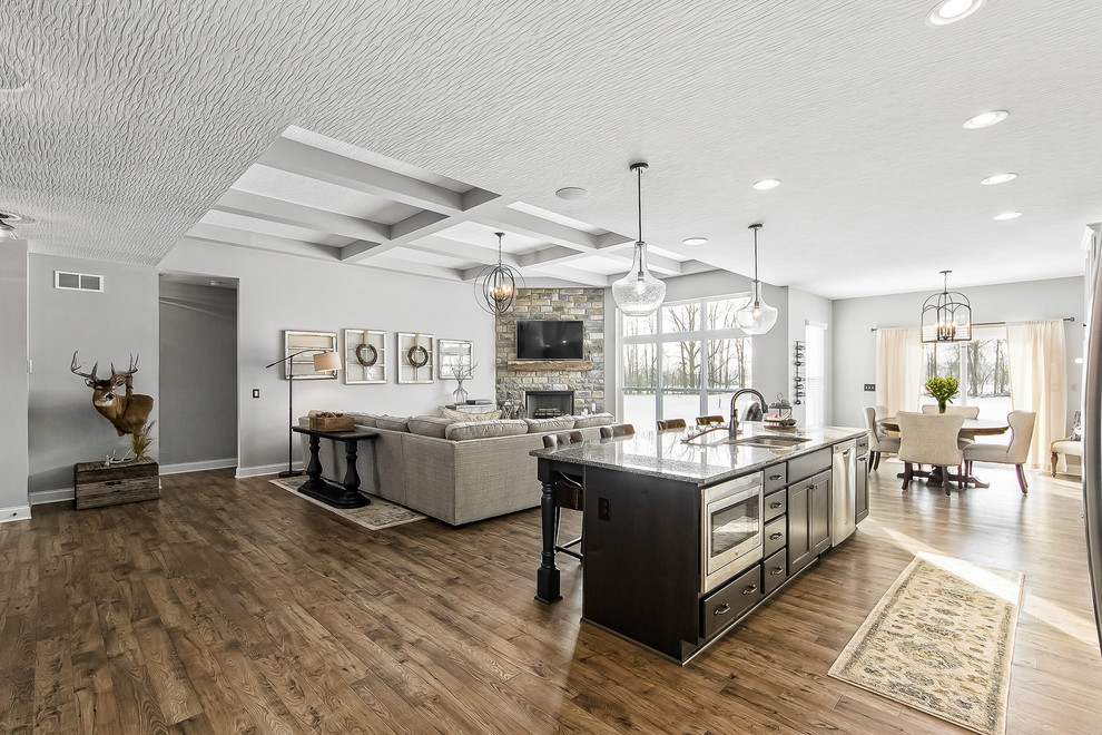 Farmhouse galley medium tone wood floor and brown floor open concept kitchen photo in Columbus with a double-bowl sink, flat-panel cabinets, black cabinets, stainless steel appliances, an island and gray countertops