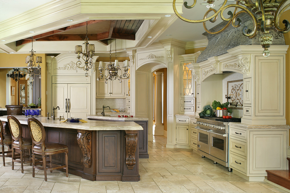Eat-in kitchen - large traditional l-shaped travertine floor eat-in kitchen idea in New York with a farmhouse sink, beaded inset cabinets, white cabinets, limestone countertops, beige backsplash, stone tile backsplash, paneled appliances and two islands