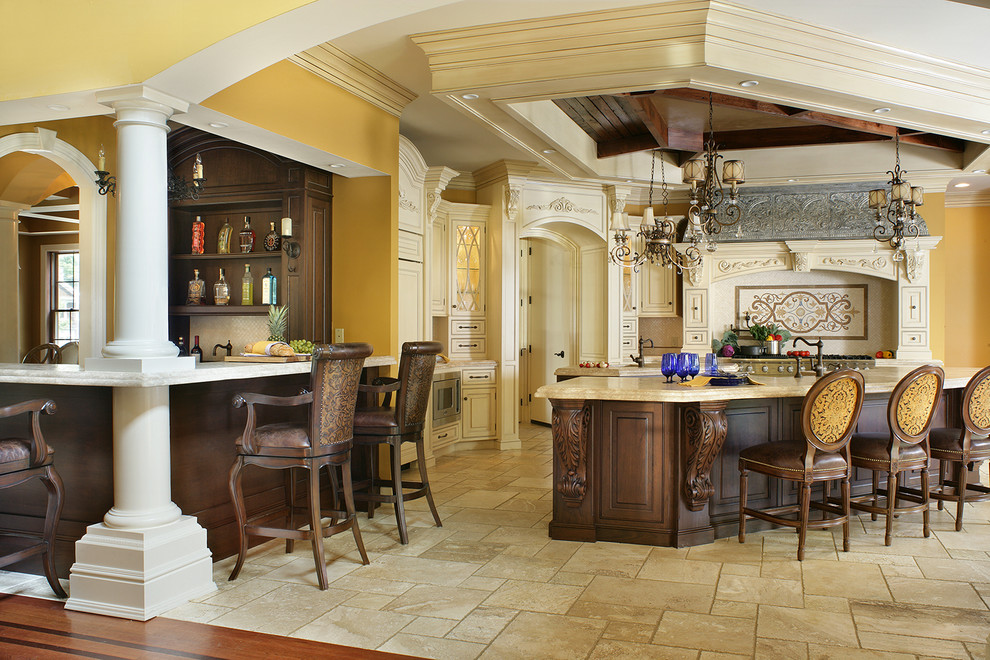 Example of a large classic l-shaped travertine floor eat-in kitchen design in New York with a farmhouse sink, beaded inset cabinets, white cabinets, limestone countertops, beige backsplash, stone tile backsplash, paneled appliances and two islands