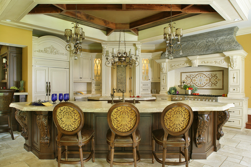 Inspiration for a large timeless l-shaped travertine floor eat-in kitchen remodel in New York with a farmhouse sink, beaded inset cabinets, white cabinets, limestone countertops, beige backsplash, stone tile backsplash, paneled appliances and two islands