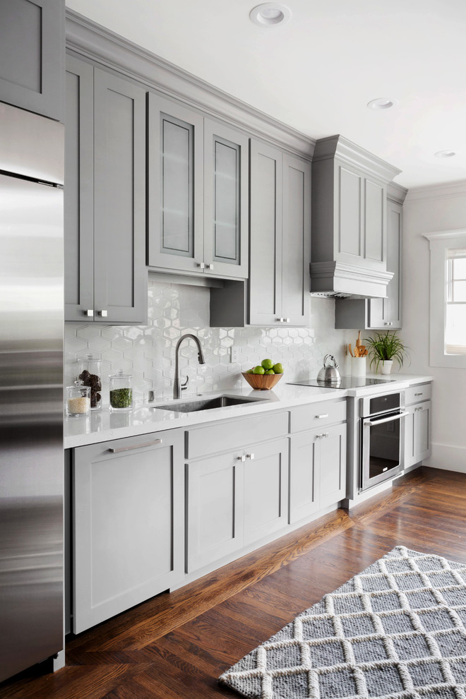 Large transitional single-wall dark wood floor kitchen photo in San Francisco with an undermount sink, shaker cabinets, gray cabinets, solid surface countertops, white backsplash, ceramic backsplash and stainless steel appliances