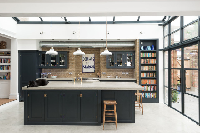 Design ideas for a classic kitchen in London with glass-front cabinets, blue cabinets, concrete flooring and an island.