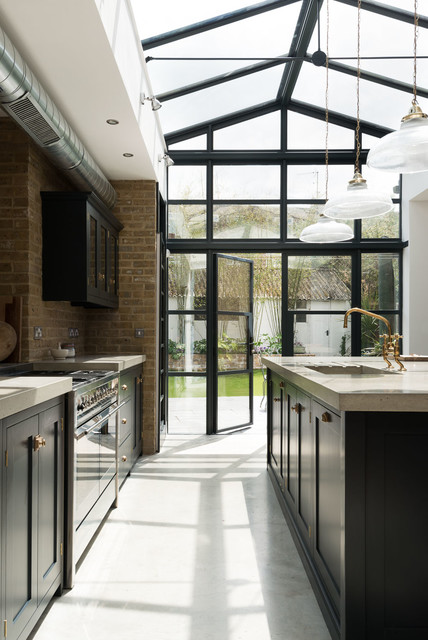 This is an example of a classic kitchen in London with shaker cabinets, concrete flooring, an island and black cabinets.