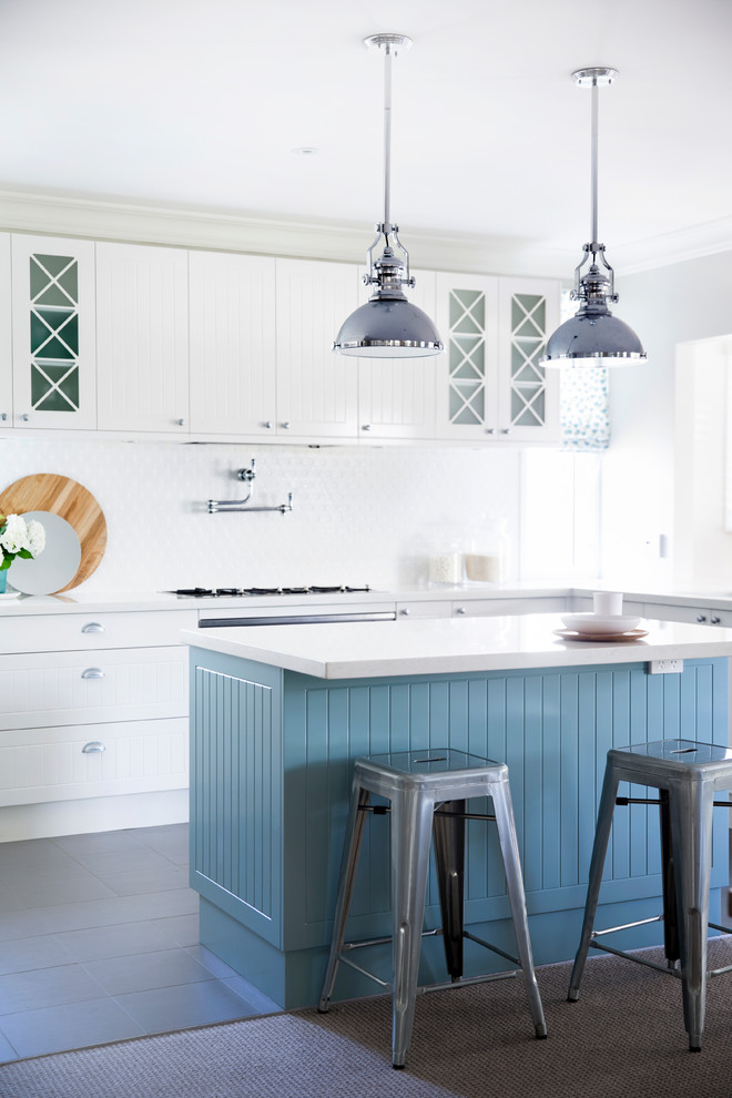 Mid-sized eat-in kitchen photo in Sydney with raised-panel cabinets, white cabinets, white backsplash, stainless steel appliances and an island