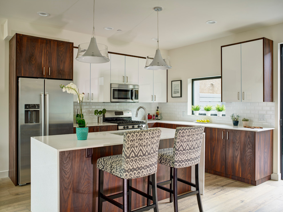 Eat-in kitchen - mid-sized contemporary l-shaped light wood floor eat-in kitchen idea in Los Angeles with flat-panel cabinets, dark wood cabinets, white backsplash, subway tile backsplash, stainless steel appliances, an island, an undermount sink and solid surface countertops