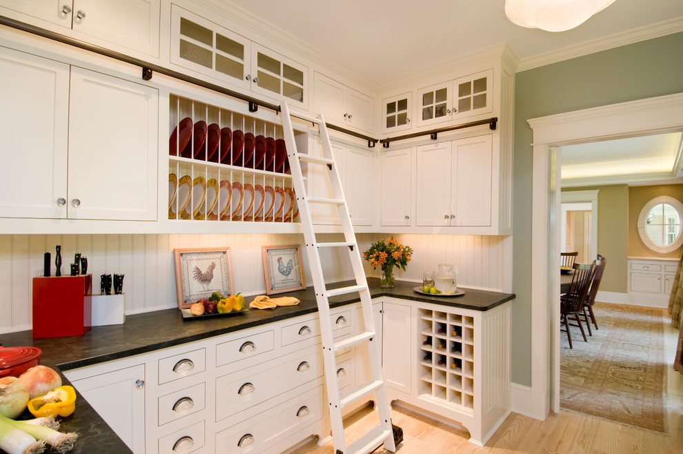 Example of a classic kitchen design in Boston with recessed-panel cabinets, white cabinets and white backsplash