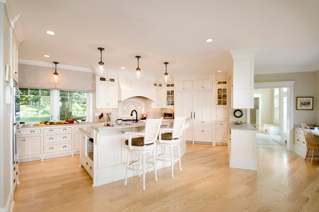Example of a classic u-shaped kitchen design in Boston with recessed-panel cabinets, white cabinets, beige backsplash and paneled appliances