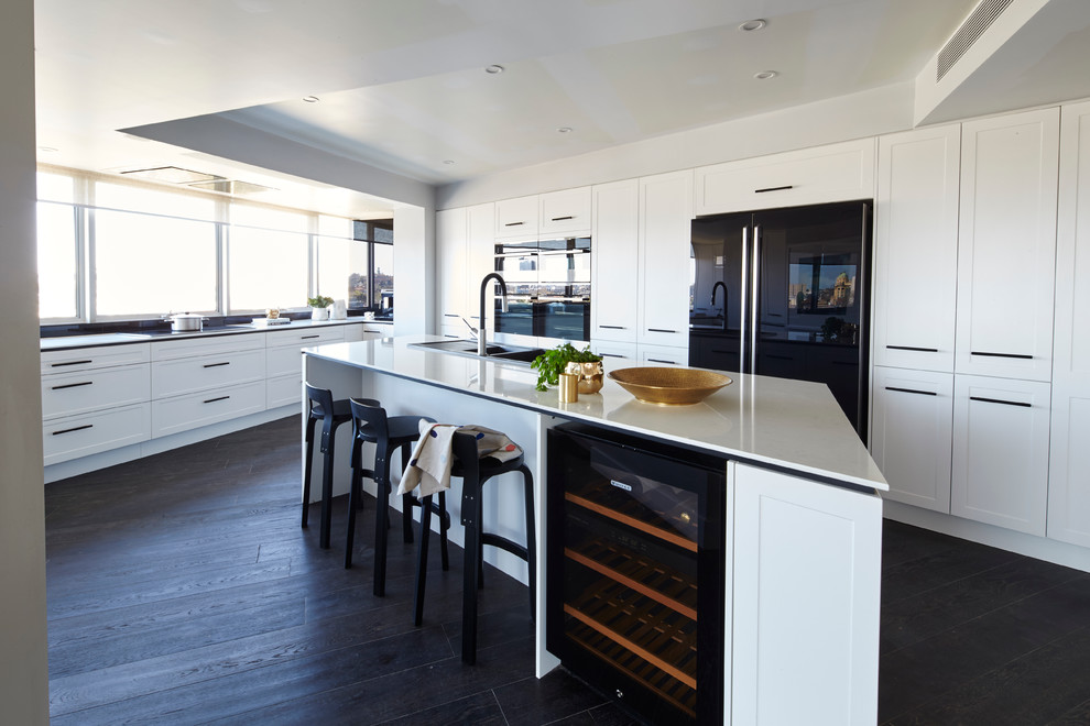 Design ideas for a large contemporary kitchen in Melbourne with a drop-in sink, recessed-panel cabinets, white cabinets, black appliances, dark hardwood floors, an island and black floor.