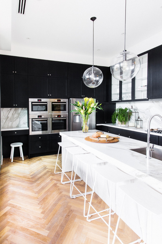 Inspiration for a transitional medium tone wood floor and beige floor kitchen remodel in Melbourne with black cabinets, marble countertops, white backsplash, stainless steel appliances and an undermount sink