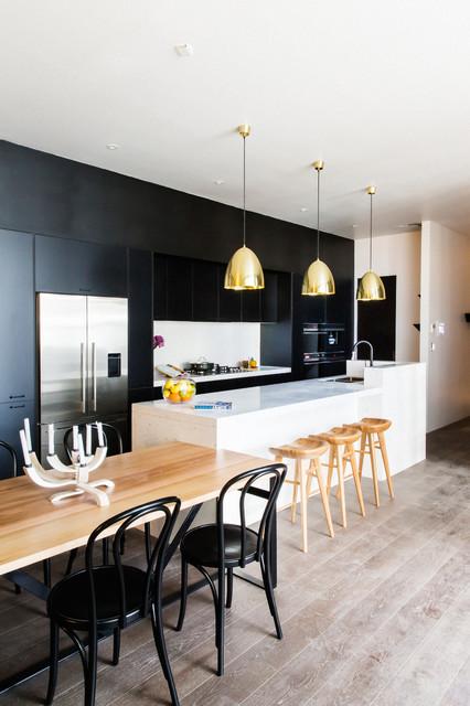 Modelo de cocina comedor de galera, contemporánea, con armarios con paneles lisos, puertas de armario negras, salpicadero blanco, suelo de madera clara y península