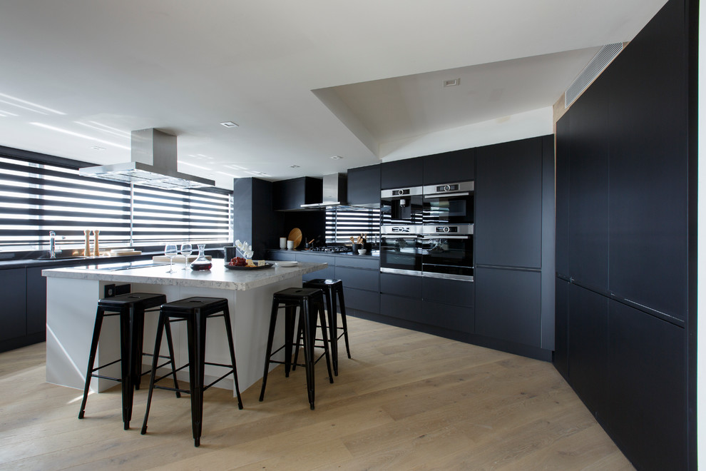 Example of a large trendy light wood floor kitchen design in Melbourne with flat-panel cabinets, marble countertops, black backsplash, an island and black appliances