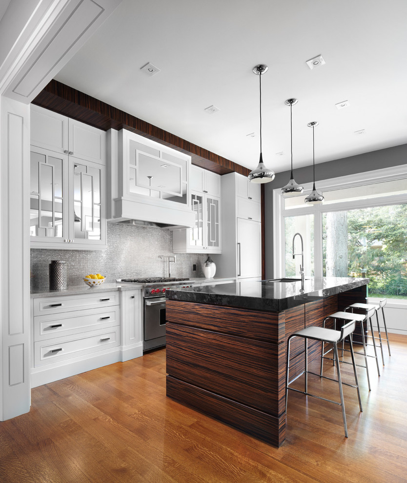 Example of a trendy galley kitchen design in Toronto with recessed-panel cabinets, granite countertops, metallic backsplash, metal backsplash and paneled appliances