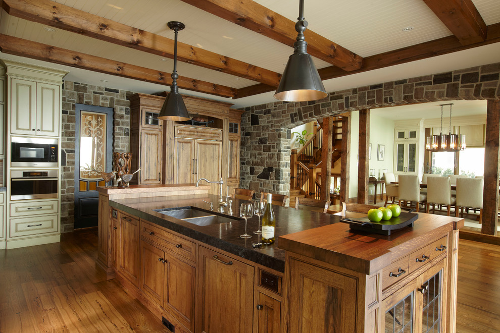 Large mountain style medium tone wood floor enclosed kitchen photo in Toronto with wood countertops, a double-bowl sink, recessed-panel cabinets, medium tone wood cabinets, stainless steel appliances and an island