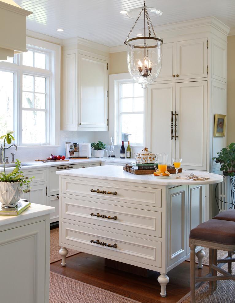 Foto di una cucina ad U tradizionale con lavello sottopiano, ante con riquadro incassato, ante bianche, paraspruzzi bianco, elettrodomestici da incasso, parquet scuro e isola