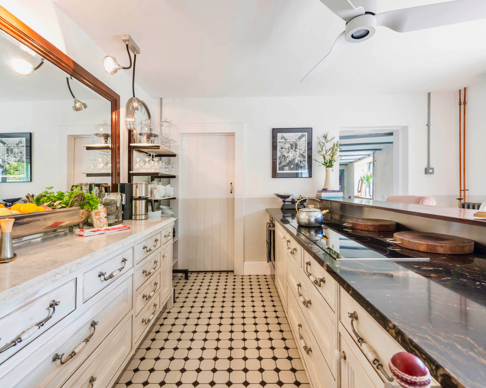 Example of an eclectic galley multicolored floor kitchen design in Hampshire with recessed-panel cabinets, white cabinets and white backsplash
