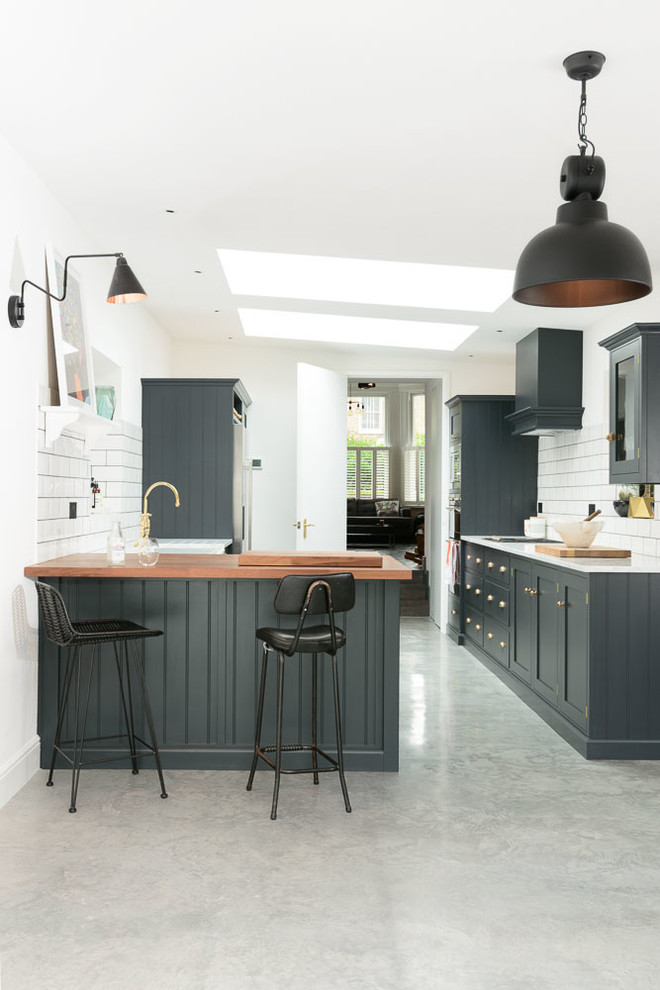 Kitchen - transitional kitchen idea in London with recessed-panel cabinets, blue cabinets, wood countertops, white backsplash, subway tile backsplash and a peninsula