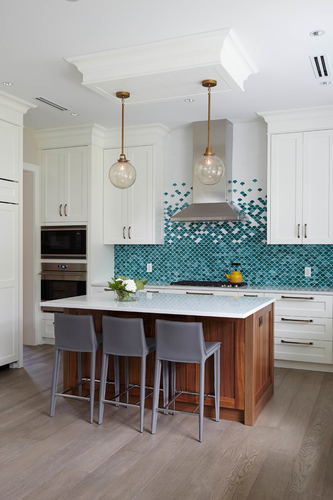Transitional medium tone wood floor kitchen photo in Vancouver with shaker cabinets, white cabinets, blue backsplash, mosaic tile backsplash, stainless steel appliances and an island