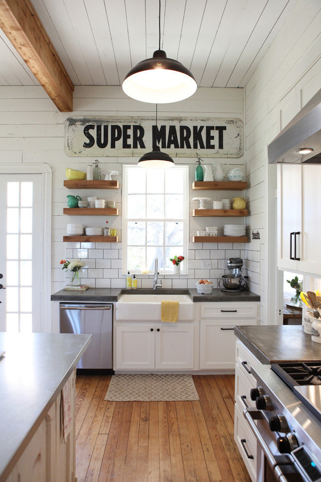 Inspiration for a mid-sized farmhouse medium tone wood floor kitchen remodel in Austin with a farmhouse sink, concrete countertops, white backsplash, subway tile backsplash, stainless steel appliances and an island