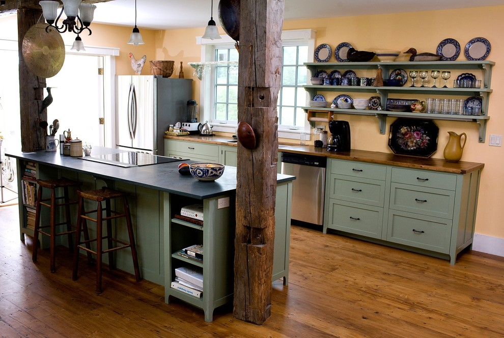 Inspiration for a farmhouse galley kitchen remodel in Boston with stainless steel appliances, open cabinets, green cabinets and wood countertops