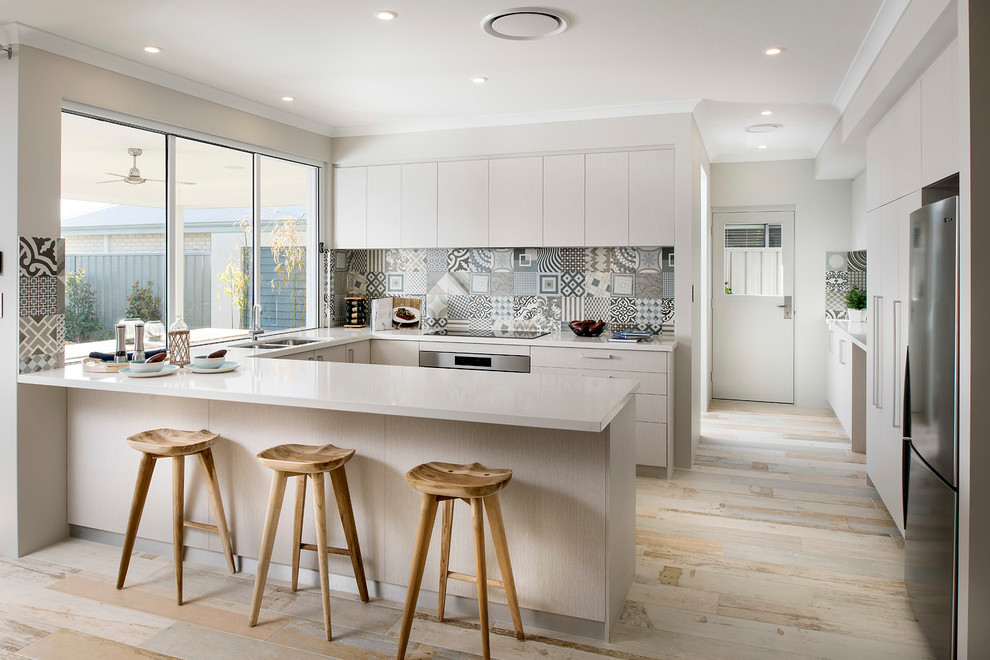 Eat-in kitchen - mid-sized scandinavian u-shaped light wood floor eat-in kitchen idea in Perth with a double-bowl sink, flat-panel cabinets, white cabinets, multicolored backsplash, ceramic backsplash, stainless steel appliances and a peninsula