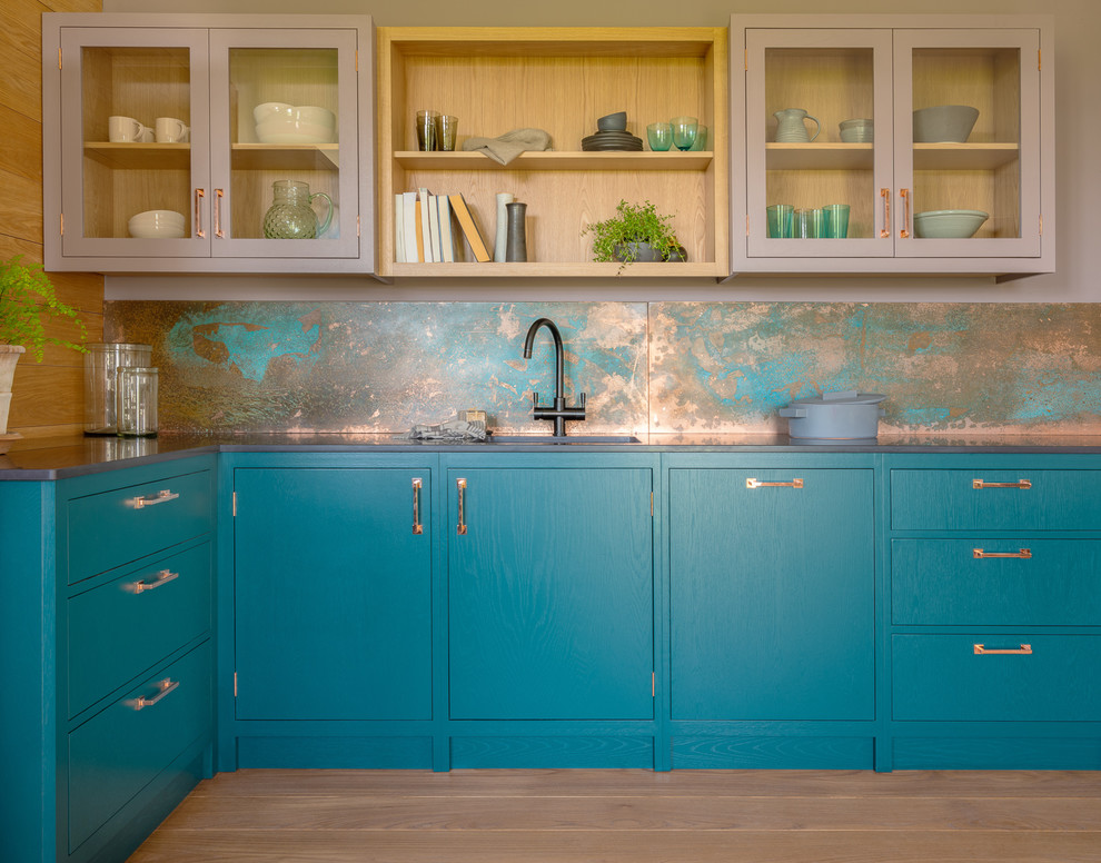 Small trendy l-shaped medium tone wood floor and brown floor open concept kitchen photo in Other with a single-bowl sink, flat-panel cabinets, quartz countertops, an island, black countertops, blue cabinets and metallic backsplash