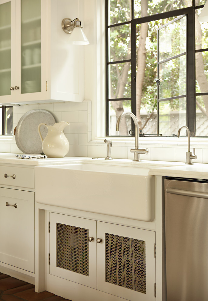 Elegant kitchen photo in Los Angeles with glass-front cabinets, subway tile backsplash and a farmhouse sink