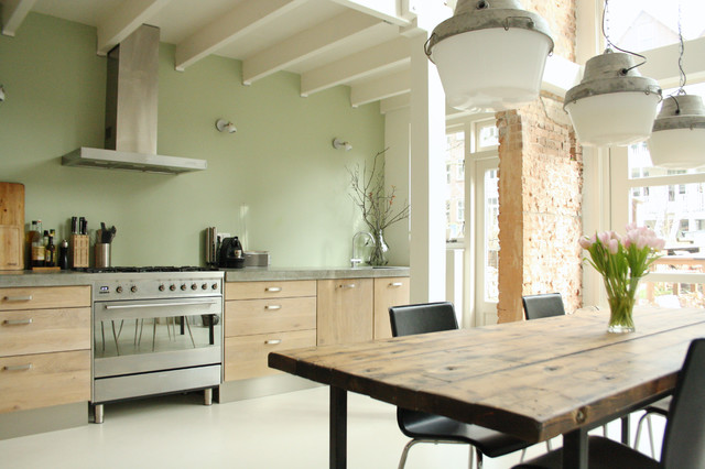 Photo of an industrial kitchen in Amsterdam with flat-panel cabinets and stainless steel appliances.