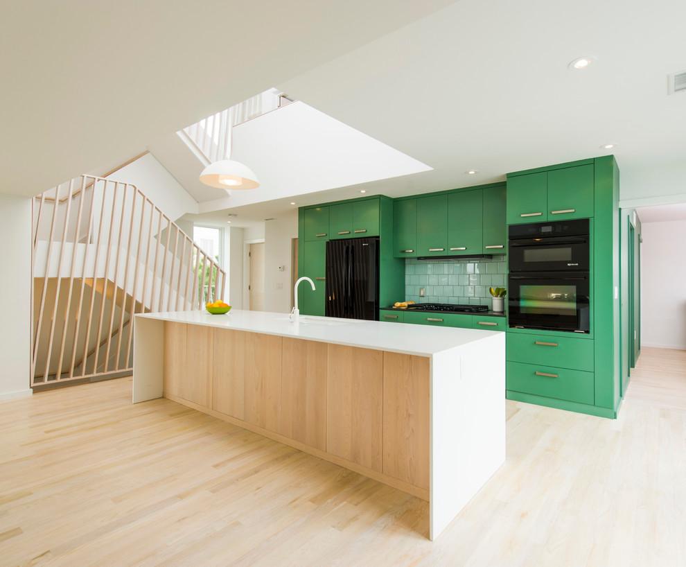 Inspiration pour une cuisine ouverte parallèle nordique avec un placard à porte plane, des portes de placards vertess, une crédence verte, un électroménager noir, un sol en bois clair et un îlot central.