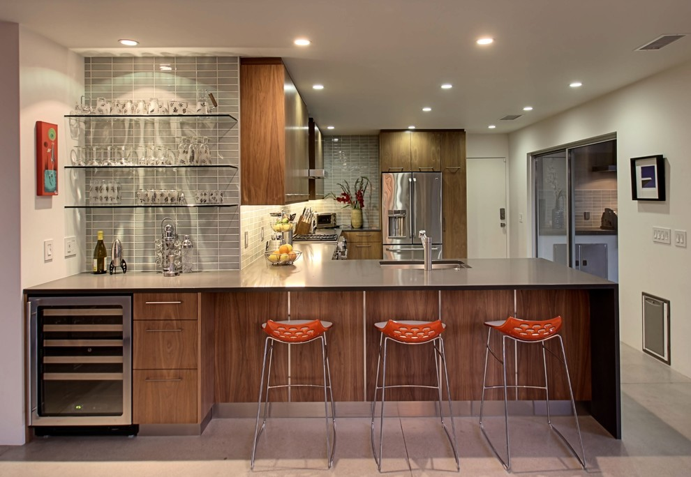 Eat-in kitchen - 1950s l-shaped concrete floor eat-in kitchen idea in Other with flat-panel cabinets, medium tone wood cabinets, gray backsplash, subway tile backsplash, stainless steel appliances and a peninsula