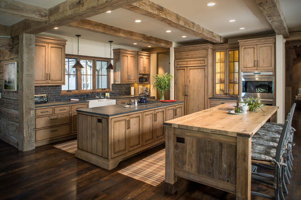 Inspiration for a rustic dark wood floor kitchen remodel in Other with wood countertops, two islands, recessed-panel cabinets, medium tone wood cabinets and paneled appliances