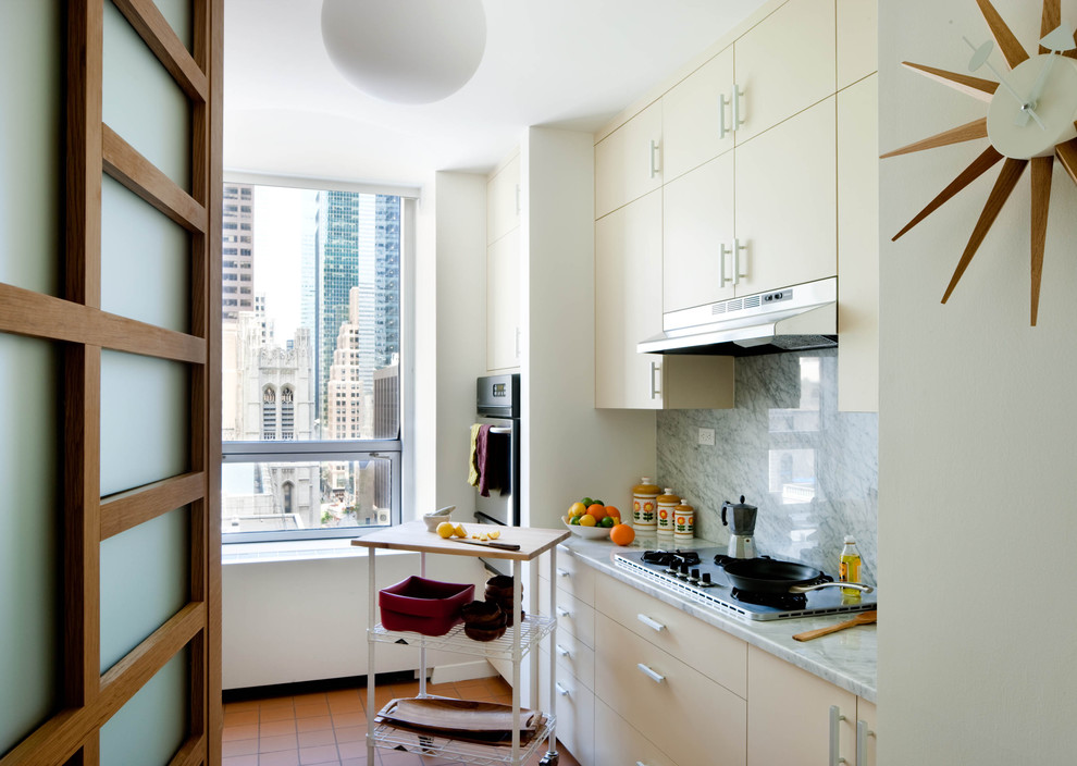 Example of a mid-century modern enclosed kitchen design in New York with marble countertops, flat-panel cabinets, white cabinets, white backsplash and stone slab backsplash