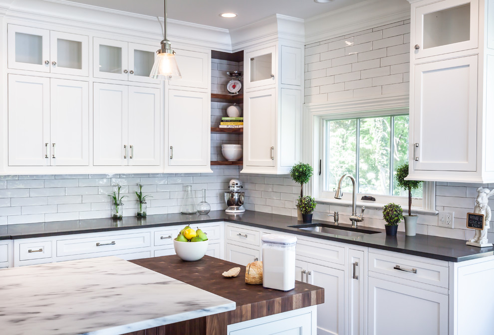 Farmhouse l-shaped kitchen photo in New York with an undermount sink, shaker cabinets, white cabinets, white backsplash, subway tile backsplash and an island