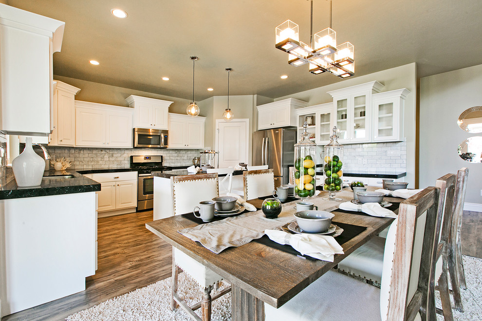 Mid-sized arts and crafts l-shaped medium tone wood floor and brown floor eat-in kitchen photo in Salt Lake City with a double-bowl sink, recessed-panel cabinets, white cabinets, quartz countertops, white backsplash, porcelain backsplash, stainless steel appliances, an island and black countertops