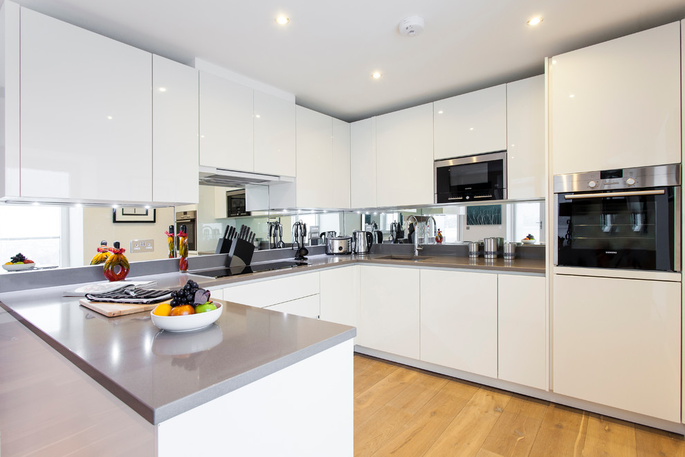 Example of a trendy kitchen design in London with flat-panel cabinets and white cabinets