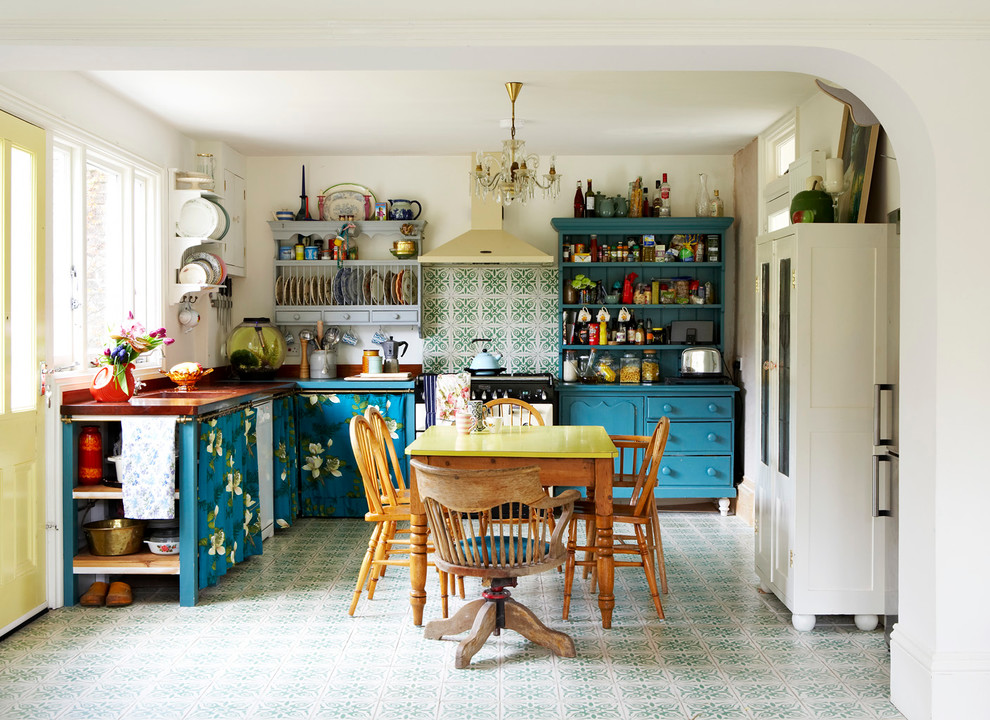 Example of an eclectic l-shaped eat-in kitchen design in Sussex with blue cabinets and green backsplash
