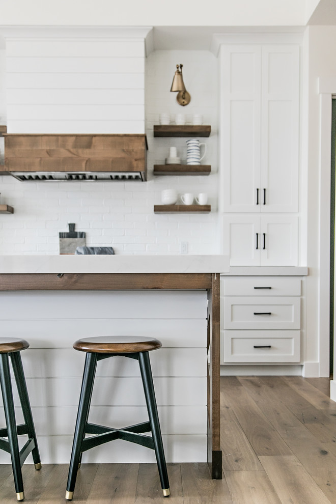 Inspiration for a mid-sized cottage l-shaped medium tone wood floor and brown floor eat-in kitchen remodel in Salt Lake City with a farmhouse sink, shaker cabinets, white cabinets, quartz countertops, white backsplash, subway tile backsplash, stainless steel appliances, an island and white countertops