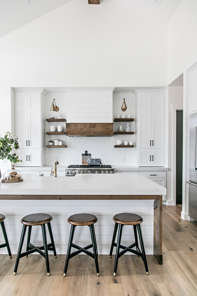 Mid-sized cottage l-shaped medium tone wood floor and brown floor eat-in kitchen photo in Salt Lake City with a farmhouse sink, shaker cabinets, white cabinets, quartz countertops, white backsplash, subway tile backsplash, stainless steel appliances, an island and white countertops