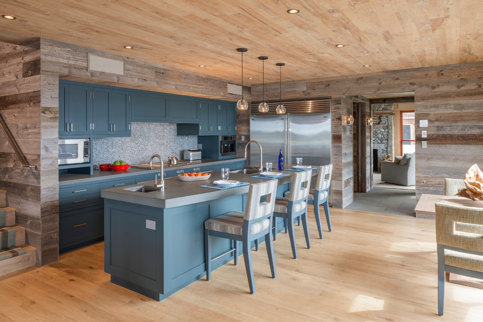 Example of a mid-sized mountain style single-wall light wood floor and brown floor eat-in kitchen design in Boston with an undermount sink, shaker cabinets, blue cabinets, multicolored backsplash, mosaic tile backsplash, stainless steel appliances, an island and gray countertops