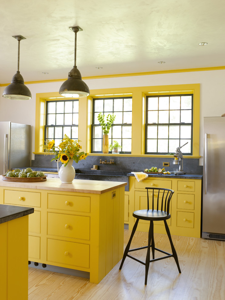 Example of a farmhouse kitchen design in New York with a farmhouse sink, beaded inset cabinets, yellow cabinets, soapstone countertops, gray backsplash, stone slab backsplash and stainless steel appliances