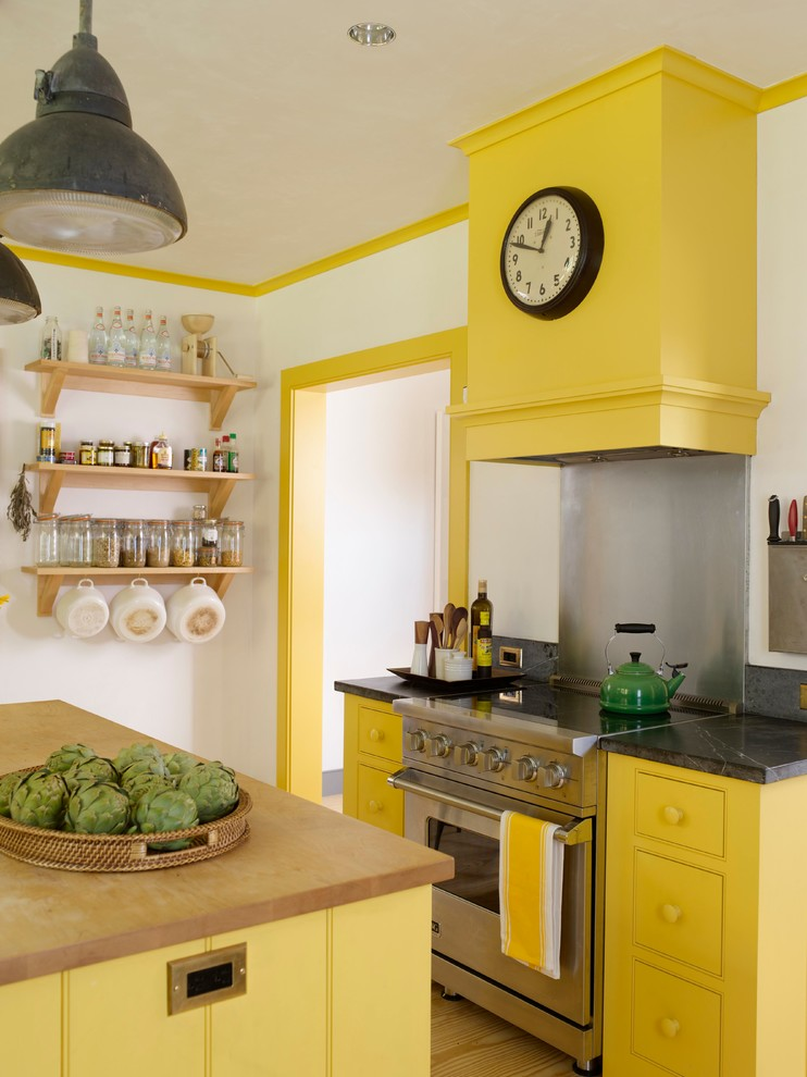 Inspiration for a cottage kitchen remodel in Bridgeport with beaded inset cabinets, yellow cabinets, soapstone countertops, metallic backsplash and stainless steel appliances
