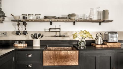 ブラックとシルバーを多用したキッチンはカッコいい空間ですね。棚につけられたマグカップを吊るすハンガーは工場で使う器具のもの。